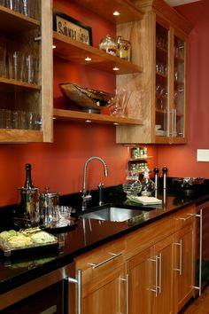 Diseño muy creativo que incorpora elementos cálido en la cocina (como la madera y el naranja intenso en las paredes) con el metal de utilizando un fregadero de la marca FRANKE y los accesorios de los gabinetes.