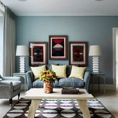 The symmetry of the stylish blue-grey living room colour scheme keeps it all looking neat.