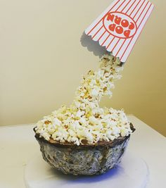 Popcorn bowl anti-gravity cake. The 'bowl' is layered ice cream, covered in a dark chocolate shell. Topped with freshly popped popcorn.