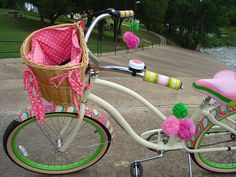 Pink girly bike with pom poms for streamers.