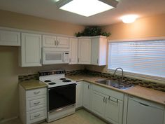 The kitchen cabinets, floor, counter tops, sink, faucet, dishwasher, and microwave are brand new.