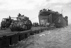 LST-21 rides at anchor whilst British M4 Sherman tanks are transferred to a Rhino Ferry.