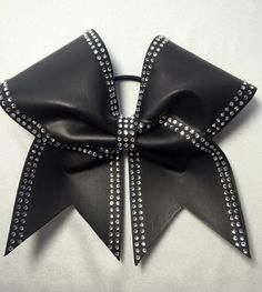 This faux leather bow is adorned with side stripes of rhinestones and a sparkly rhinestone center. Faux spandex leather makes this bow flexible but it still has a leather look!