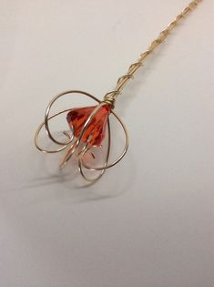 This wand was inspired by the queen of hearts. Its a fantastic scepter with the top curled inward and the red stone in the centre. The gold wire