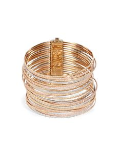 Sparkly stacks of textured yellow, rose and white gold bangles lend a dazzling twist to Carolina Bucci's statement bracelet