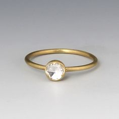 An 18k yellow gold ring with an  0.45cttw round white rose cut diamond.  Diamond measures 5.5mm in diameter.  Size 7.