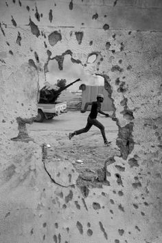 A Libyan revolutionary fighter runs for cover while attacking pro-Gadhafi forces in Sirte, Libya, Oct. 2011 (Manu Brabo/AP)  Photographer Manu Brabo. AP Photographer and 2013 Pulitzer Prize winner for Breaking News Photography Manu Brabo. Manu Brabo was born in Spain in 1981.
