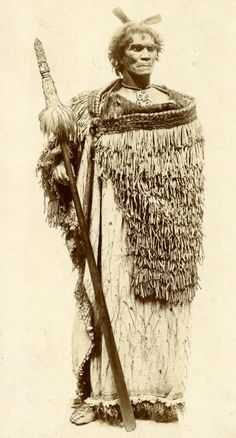 Mannequin/life caste of a Maori chief wearing a rain cape over a korowai (tag cloak); holding a taiaha (ceremonial and fighting staff), wearing a hei tiki (neck pendant), and two huia feathers in his hair. | 19th century | Photographic print; © The Trustees of the British Museum
