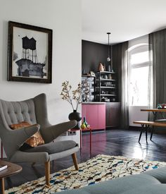 The old wood floors throughout designer Peter Fehrentz's 646-square-foot Berlin apartment are painted a dark eggplant, which help pick up the black of the kitchen wall, the vase, and the painting. The vintage PP19 armchair is by Hans J. Wegner for PP Møbler.