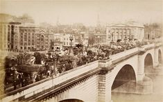 London Bridge, filled with vehicles and pedestrians in 1875. By 1902, the bridge had become so busy that the width of the pedestrian pavements were increased by one metre.