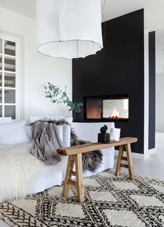 Modern black and white living room with a floating fireplace, Beni Ourain Moroccan rug and paper pendant light.