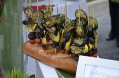 Roasted veggies on a stick. Propped up by a loaf of italian bread! Edible food props.... So easy a 3 year old could do it! Did we mention delicious!   Visit www.facebook.com/tabletopcatering  For more info and inspiring ideas for your next party!