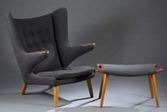 """A Hans Wegner Papa Bear chair with ottoman. Mid 20th century. Upholstered in black wool with wood frame. Chair: 39""""h x 35 1/2""""w x 36 1/2""""d. Ottoman: 16""""h x 27 1/2""""w 16""""d. Price Realized: $9,000, Quinn's Auction Galleries"""