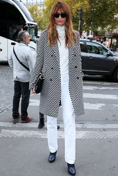 Caroline de Maigret wears a white turtleneck, white trousers, a checked black and white coat, and black boots