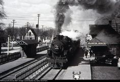 "Beautiful action shot by an unknown photographer of Chicago & Noth Western 4-6-2 Mikado #1538 pulling into the passenger staton in Arlington Heights, IL. Built by Alco-Schenectady in 1909, this group of Pacifics (#1530-1540) were the only Es delivered with 23"" diameter cylinders - both the North Western and Alco came to the same conclusion and adopted 25"" cylinders beginnning with 1541. Later, CNW shops superheated the class. The date is approximate based on the parked autos near the…"