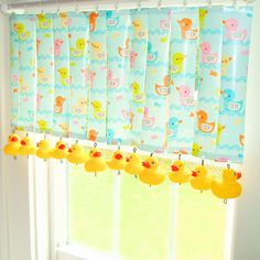 This window treatment utilizes baby shower gift wrap and Dollar Tree rubber duckies for an adorable and unexpected theme.