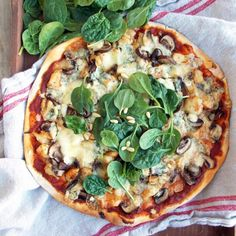 Delicious, hearty and earthy pizza topped with chicken, mushrooms, blue cheese and garnished with spinach and pine nuts.
