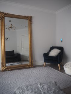 Living room with gold mirror and blue velvet chair