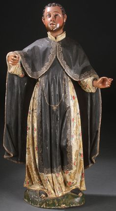 A CARVED AND POLYCHROMED WOOD FIGURE OF SAINT MARTIN DE PORRES, PERUVIAN, 18TH CENTURY. Carved in full round, the head set with glass eyes.