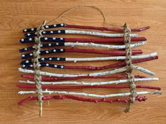 Rustic, primitive American flag made from sticks I found in the yard, acrylic craft paint and twine. Perfect for 4th of July, Labor Day, Memorial Day or Americana decor.