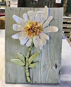 10x14- Mosaic 3 D flower. Boho wall art. Made from recycled pottery in white. The center in hand cut stained glass in yellows and oranges. Stems are a pale green recycled pottery. I hand cut ever piece. Its on recycled barn wood that I painted a pale green. Ready to hang.