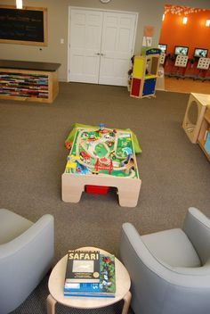 Adding a train table and adult seating in a children's library invites patrons to stay for awhile! Check out the recycled book circulation desk in the background. www.southbutlerlibrary.org