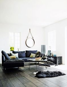 A moody and dark Scandinavian living room with navy sofa and hanging round mirror