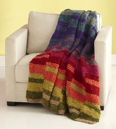 Curl up with this Super Easy Lap Blanket. Knit with the garter stitch, this colorful afghan pattern is perfect for anyone who wants to learn how to knit a blanket that is sure to keep them nice and toasty during the winter months.