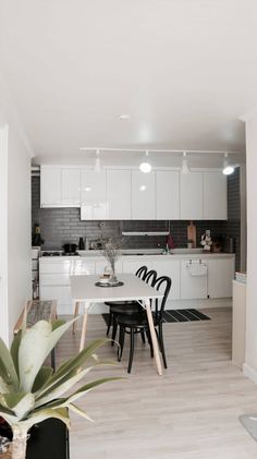Lovely, small, modern kitchen and dining room with light floorboards, glossy whie cupboards and black dining chairs. by toki