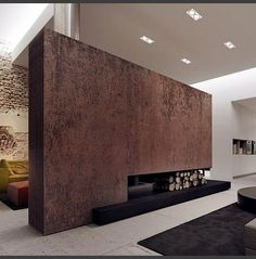 In love with the rusted wall, the simple fireplace, the decaying brick. This room is full of texture. Kler showroom interior design by Tamizo Architects group