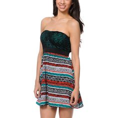 Hit the beach party scene in the Nia Tribal Print dress from Empyre Girls. This strapless dress features a teal bodice with a black crochet overlay and ruching at the front for added shape. The empire waist, smocked back, and lightweight skirt make for a perfect fit and coral, teal, black and white print adds a native pattern that looks great over a bikini or paired with strappy sandals.