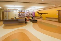 PHOTO TOUR: Shriners Hospital for Children, Montreal, Quebec | Healthcare Design --- The second floor rehabilitation services and the conference center are in the Badlands. A trail of large dinosaur footprints set into the vinyl flooring lead to the physical therapy room, where several of the gentle giants can be found stretching up its double-height walls. Photo: David Dworkind
