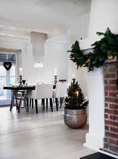 winter white kitchen, sawhorse table, potted tree, and a crystal chandelier that definitely brings in the wow factor.