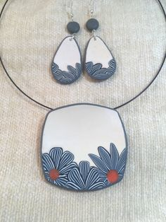 By Debby Wakley Square round pendant in white with blue flowers edging the pendant and earrings. Made using Premo polymer clay