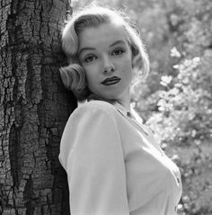 Marilyn Monroe August 1950 unpublished photos from Griffith Park. she was an unknown blonde bombshell at the time, being photographed for Life magazine-although these never made it into print. beautiful, young, fresh-faced, signature red lipstick. black and white photography in the woods with a tree