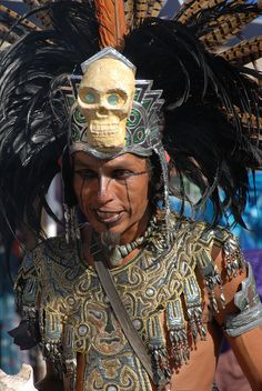 This Aztec dancer wears a feather headdress decorated with a  green-eyed skull. Zocalo. Mexico City