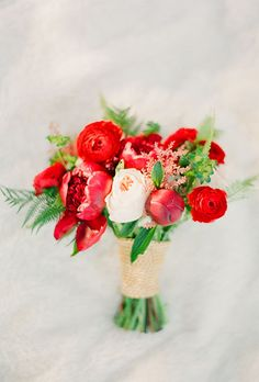 Brides.com: . A red bouquet made of peonies, ranunculus, and greenery created by Blue Bouquet.