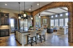 A memorable brick arch links this elegant kitchen and great room. Newly built homes in the Quisana community by Standard Pacific Homes. Scottsdale, AZ.
