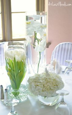 All white wedding flowers. Centerpiece of submerged phalaenopsis orchids, tulips and bowls of dutch hydrangea. Mine would be ivory spray roses in the tall vase, Sahara roses in the medium vase, and ivory hydrangea in the bowls. Tulip Wedding, All White Wedding, White Wedding Flowers, Trendy Wedding, White Weddings, White Flowers, Floral Centerpieces, Wedding Centerpieces, Wedding Bouquets