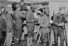 American soldiers getting their bowls of chocolate and rolls in the American Red Cross canteen at Toulouse, France. Circa 1917-1919.