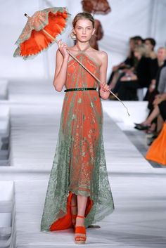 Long halter dress with fishtail (high-low) hemline. Bright orange solid under juniper green lace. With a charming parasol. Hermes 2006