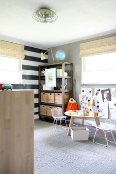 striped wall , chairs, magnetic boards below window for art work, rug for accent