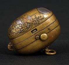 A Sentoku Bronze Netsuke - 19th Century. A good rare and functional tinder box netsuke. This unusual piece is in sentoku bronze with an inlaid silver moon above a mountain shrine dwelling. The mechanism cocks like a flintlock and strikes a plate.