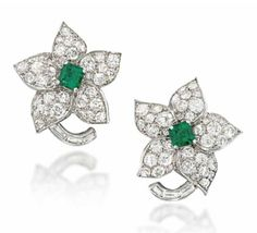 A PAIR OF EMERALD AND DIAMOND EARRINGS, BY VAN CLEEF & ARPELS  Of flowerhead design, each square cut-cornered emerald centre to a pavé-set circular-cut diamond five petal surround, raised on a curving baguette-cut diamond stem, circa 1950, French marks for platinum and gold, 2.5cm long, post fittings later replacements, with maker's pouch Signed Van Cleef & Arpels Paris, no.50411