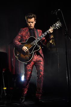 Harry Styles in a custom burgundy brocade Gucci suit performing in New York on September 28