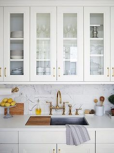 Rich materials including brass and marble accent the kitchen for a crisp and clean look that's also warm and inviting.