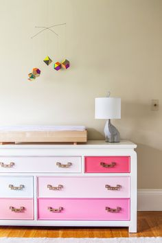 A geometric mobile above a dresser with drawers in shades of pink #nursery #pink