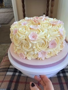 Vanilla rose buttercream cake with pink fondant flowers and pearls for decoration