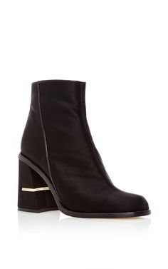 2d35c6b58ea9 This   Tibi   bootie features a satin body with a rounded toe and a  matching block heel with metallic accent.