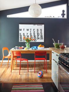 Red & Orange + Dark Teal: If your kitchen is homework central, don't try to fight it - embrace it! Make the space feel like home for the kids, too. This is a fun departure from matching chairs - they're different but they still go together because of their structure and finish. The large font calendar on the wall makes a great statement!